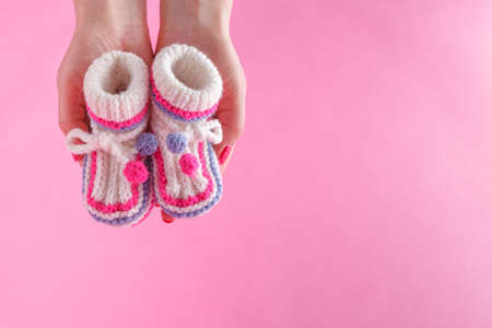 Motherhood concept. Female hold tiny newborn booties