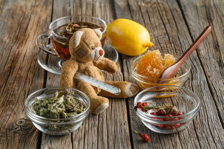 glass thermometer: Temperature measurement with toy bear. Health warm tea for flu prevention. Stock Photo