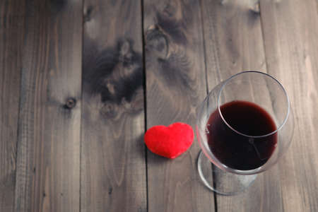 Glass of red wine on wooden table and heart. View from top Standard-Bild