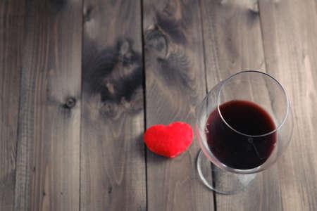 Vaso de vino tinto en la mesa de madera y corazón. Vista desde arriba Foto de archivo