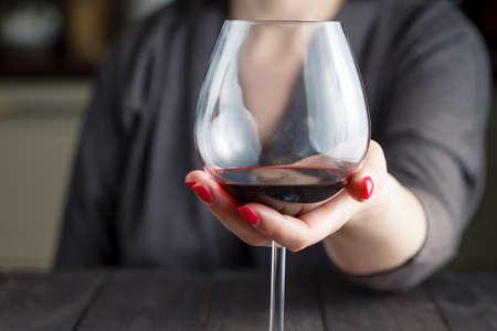 alcool: femme, boire de l'alcool sur fond sombre. Focus sur un verre de vin