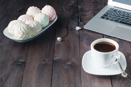 netbooks: White laptop with coffee cup and marshmallow on old wooden table. Stock Photo