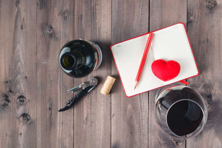 redwine: Red wine glass and notebook on table Stock Photo