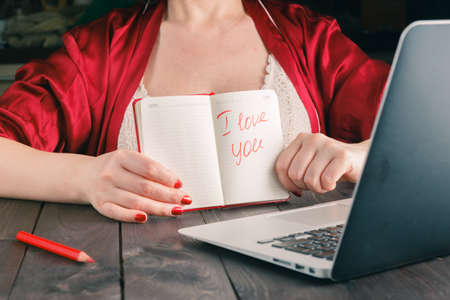 distance: Woman show phrase i love you to friend at laptop web cam Stock Photo