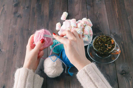 two womens hands, gain loop for knitting