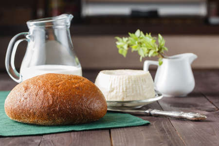 ewes: Fresh feta cheese with milk and bread on a wooden table