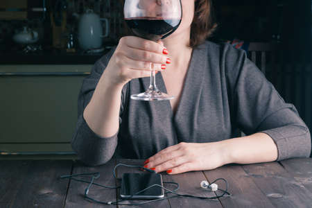 heartsickness: sad thinkful woman sitting with a glass of red wine in her kitchen Stock Photo