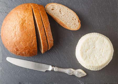 queso fresco blanco: Desayuno con queso cottage, vaso de leche, queso búlgaro y bocadillos, en mesa de madera blanca Foto de archivo