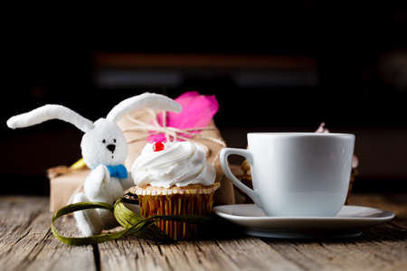 butter icing: cupcake and rabbit toy with cup of coffee Stock Photo