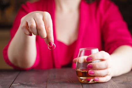 marido y mujer: Mujer quitarse el anillo de bodas y beber whisky en la mesa de madera