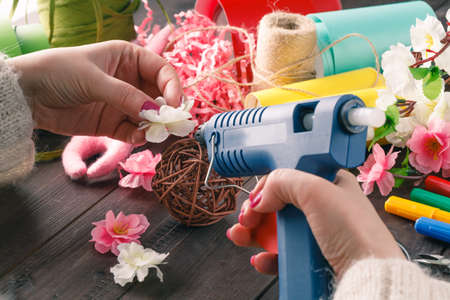 Woman make floral decor with melt glue gun Stock Photo