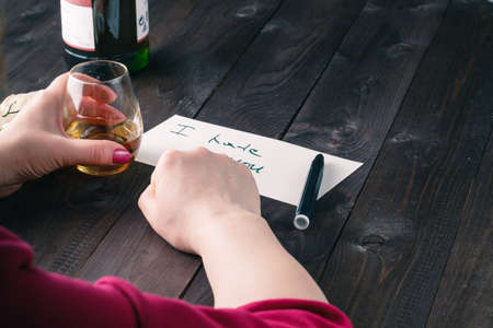 Woman drink alcohol and write message to bad partner Stock Photo