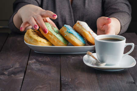 drink me: Woman take donuts and hold message eat me Stock Photo