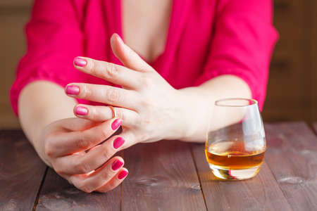 unfaithful: Woman take off wedding ring and drink whiskey on wooden table