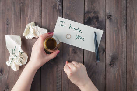 top hate: Woman drink alcohol and write message to bad partner Stock Photo