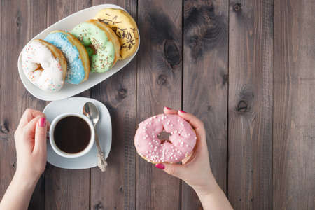 Woman eat donut and drink coffee, breakfast concept. Top view