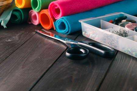 kit de costura: Kit de costura. Tijeras, bobinas con hilos, botones y agujas en la mesa de madera rústica