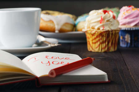 teenagers love: Breakfast concept. Donuts and love message in notebook