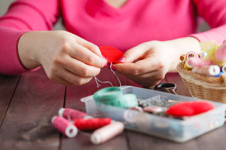 conceptual symbol: Woman sews red heart shaped toy by needle, conceptual symbol of love