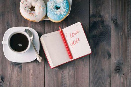you black: Rosquillas y amo mensaje en el cuaderno Foto de archivo