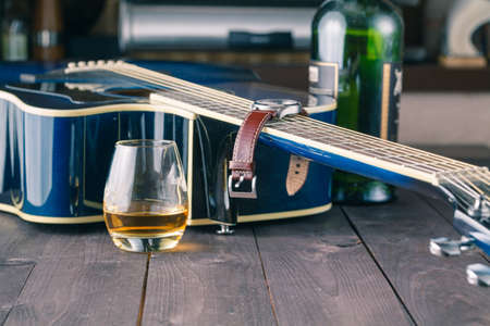 fingerboard: Guitar side view, strings and fingerboard with glass of alcohol on table Stock Photo