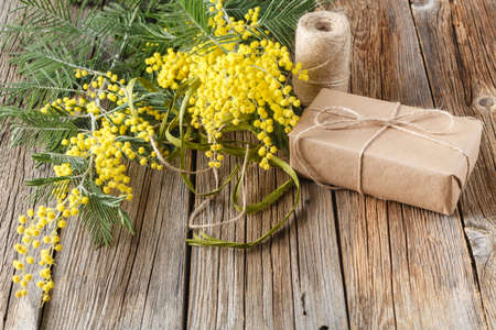 wrapped gift: top view paper wrapped gift with yellow spring flowers Stock Photo