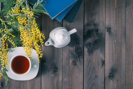 retiring: Cup of tea and books on wooden table. Spring yellow flowers Stock Photo