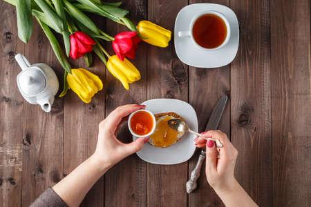 comiendo pan: Mujer que come el pan con mermelada. Ramo de tulipanes en la mesa de madera