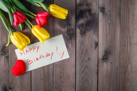 arreglo de flores: Mensaje del feliz cumpleaños y tulipanes de flores en la mesa