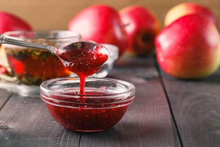 mermelada: mermelada de frambuesa en una cuchara de mesa de madera oscura