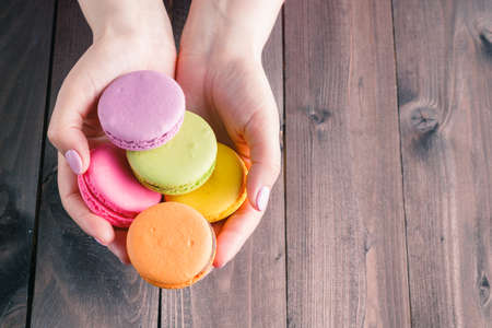 women's hands: Womens hands holding macaroons on rustic table