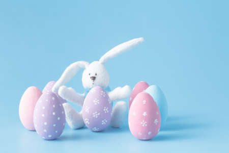lop eared: Toy rabbit with Easter eggs on blue Stock Photo