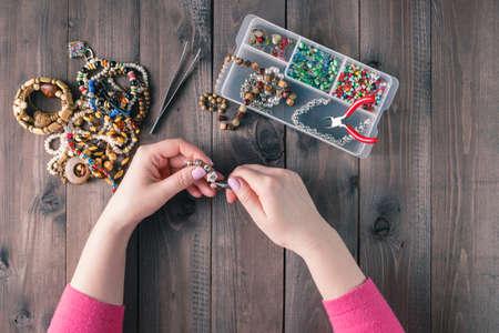 Fabricación de joyas hechas a mano. Caja con granos en el fondo de madera vieja. accesorios hechos a mano. Vista superior