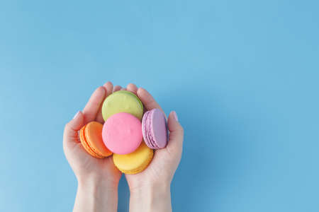 raspberry dress: Girl holding colorful French macarons in hands Stock Photo