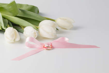 alliance: Golden wedding rings over pink ribbon and white tulips