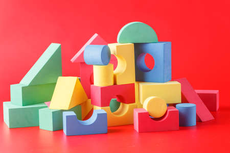 photo of object s: toy castle from color blocks on a red background