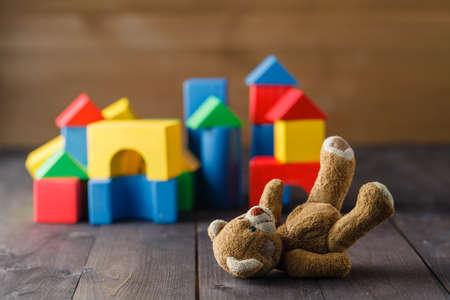 bilding: Retro Bear toy alone on wooden floor with bilding blocks