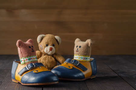 modish: Baby boots and toy doll on wooden table over wall grunge background, vintage style Stock Photo