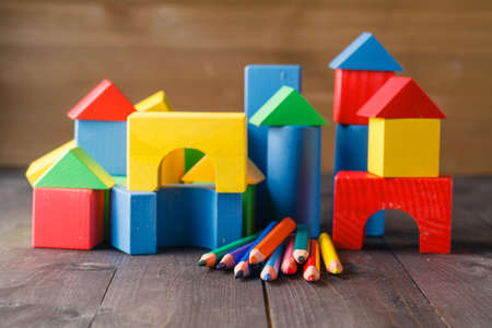 child standing: Different colors of pencils ontable with building blocks
