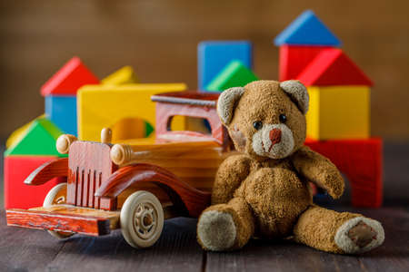 assemble: House made of wooden blocks to assemble, near atoy and a wooden toy car Stock Photo