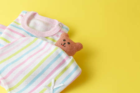 infantile: Baby clothing on a yellow background