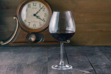 Vaso de vino tinto con fondo de reloj Foto de archivo - 56407682