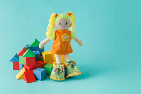 lock block: Kid doll with wooden building blocks on plain background