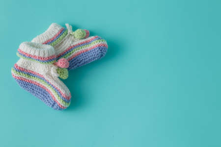 booties: Newborn announcement template. Handmade knitted booties on plain background
