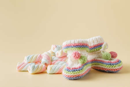fondo para bebe: Newborn announcement concept. Knitted booties on beige background with sweets