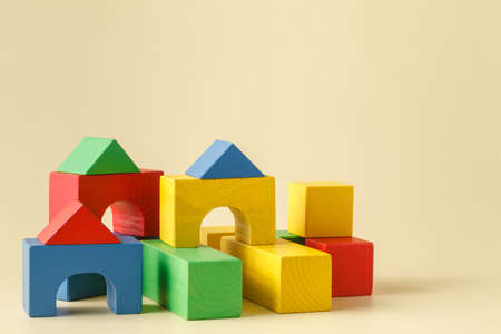 dark backgrounds: The toy castle from color blocks isolated on beige background Stock Photo