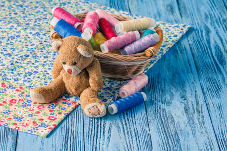 soft toy: threads in basket and soft toy on blue table