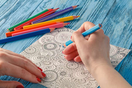 tendency: adult coloring books colored pencils anti-stress tendency. Hobbies womans hands painting stress relief painter Stock Photo