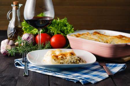 Cena mediterránea con lasaña y vaso de vino tinto Foto de archivo - 56446431