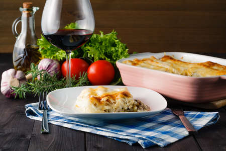 mediterranean dinner with lasagne and glass of red wine